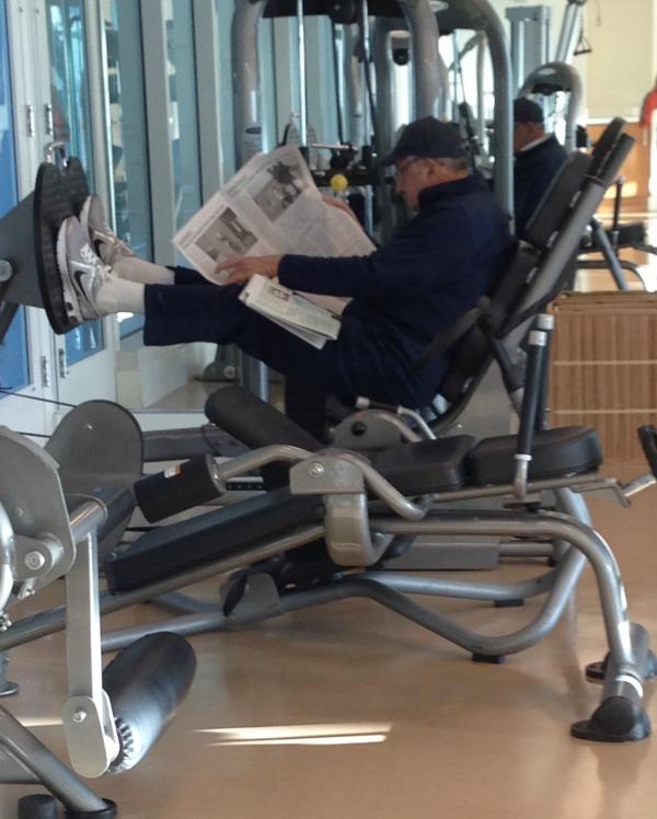 man reading while on leg press machine, simply social blog